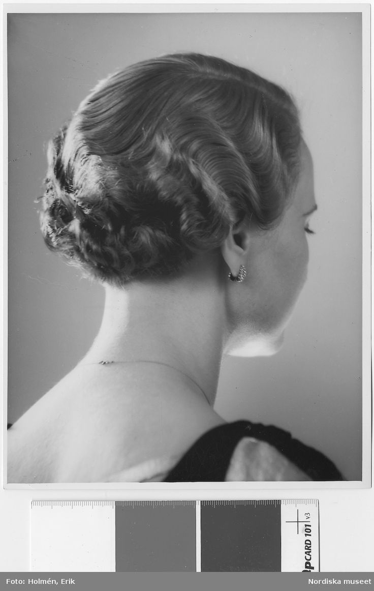 """Kvinna med kort, vågig frisyr. Text med blyerts på baksidan: Hygieniska avd. Frisyrer (fru M Oldenburg, Arden)"""". Fotograf: Erik Holmén"""
