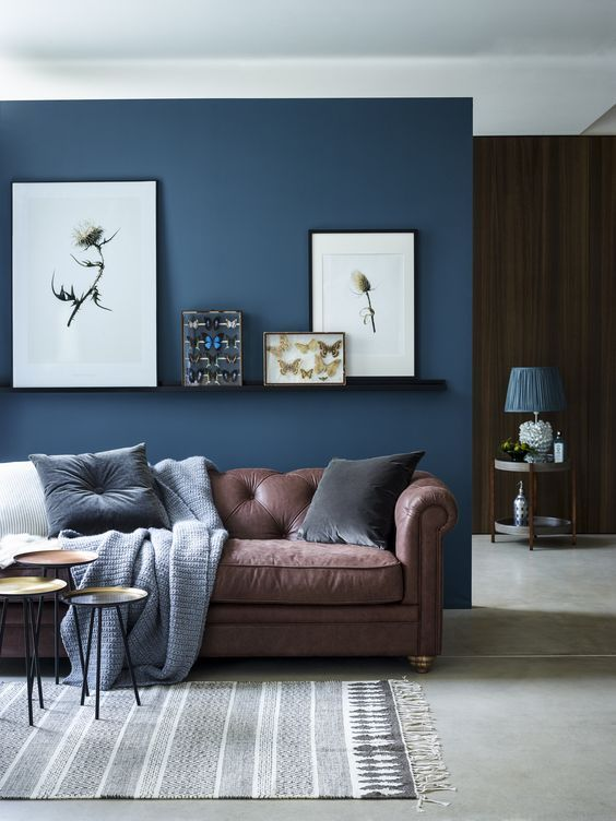chic seating area with a brown sofa and a navy accent wall and