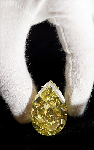 'The Sun-Drop Diamond' is displayed during a press preview on November 9, 2011 in Geneva. One of the world's largest diamonds, a pear-shaped 110.3-carat yellow rock, will go under the hammer in Geneva on November 15, 2011 expecting to fetch about $15 million. The Sun-Drop diamond, discovered in South Africa last year, is billed by Sotheby's as the 'world's largest known pear-shaped fancy vivid yellow diamond'. AFP PHOTO / FABRICE COFFRINI (Photo credit should read FABRICE COFFRINI/AFP/Getty…