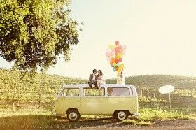 An example of an engagement photoshoot idea - sitting on top of the car with the vineyard in the backdrop with balloons