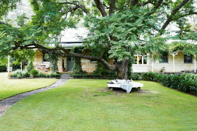The base of the jacaranda tree is a favourite spot for the owners of this 1890s sandstone home. Having weather-tolerant furniture in favourite places, or close to hand, makes it easy for you – or your pet - to rest and relax. Photography Michael Wee