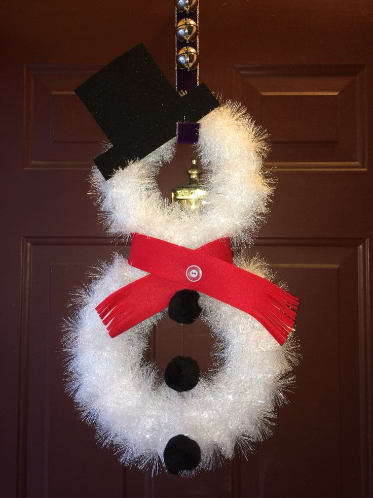 Snowman wreath made with white foam wreaths wrapped in white tinsel, felt for hat and scarf and Pom poms strung with fishing wire.