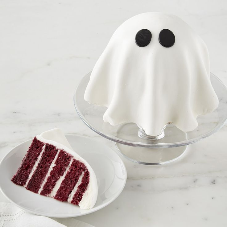 A spooky 4 layer red velvet cake shaped like a friendly ghost that is layered with vanilla cream cheese frosting and topped with a ghostly fondant cloak with two eyes cut out like a homemade bed sheet ghost costume. it's also Ectoplasm-free.