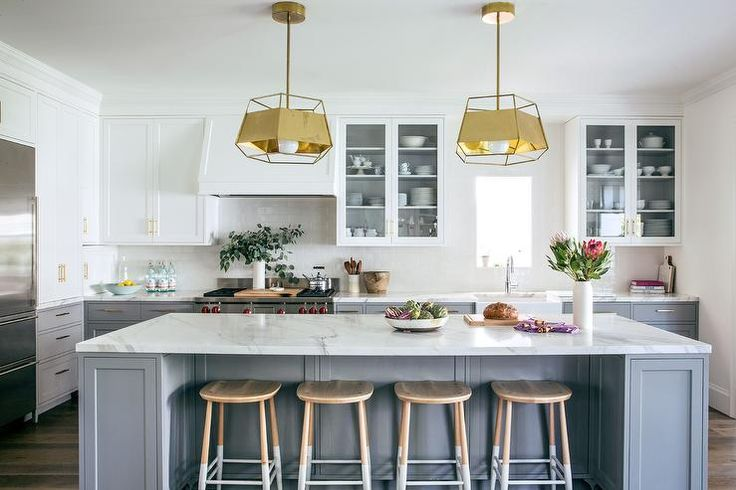 A pair of gold pendants by Lacoli and McAllister illuminating a gray kitchen island topped with white marble lined with backless dip dyed counter stools.