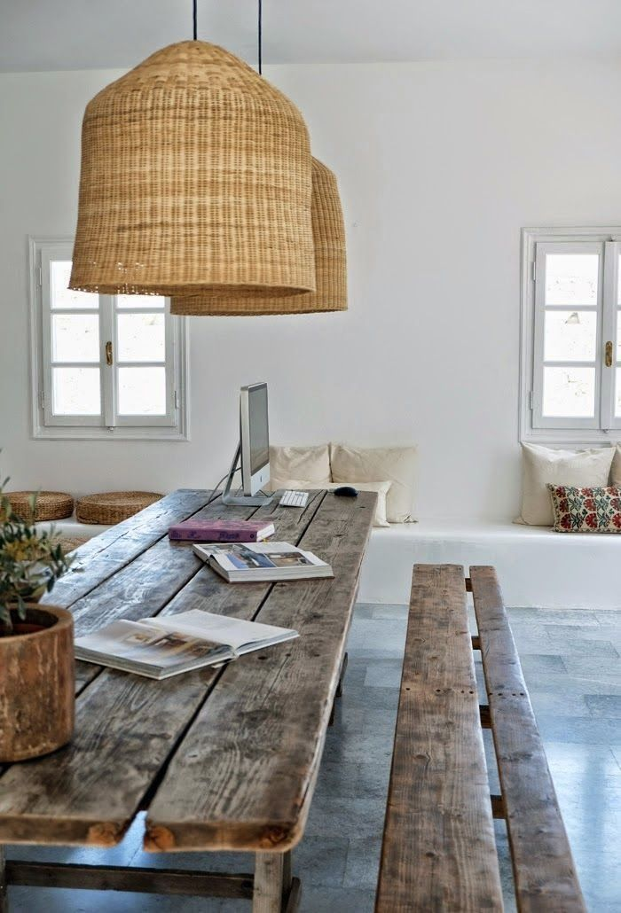 A rustic dining room that includes oversized basket pendants with a farmhouse dining table with bench seating