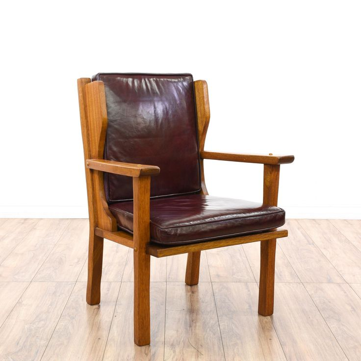 This mission style accent chair is featured in a solid wood with a rustic oak finish. This craftsman armchair has dark red leather upholstered seat cushions, a ladder back and joinery details. Stunning chair perfect for accenting a room! #americantraditional #chairs #armchair #sandiegovintage #vintagefurniture