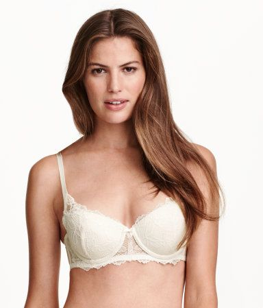 Balconette bra in lace. Padded underwire cups with removable inserts for lifting and shaping. Narrow, adjustable shoulder straps, boning in sides, and hook-and-eye fasteners at back.
