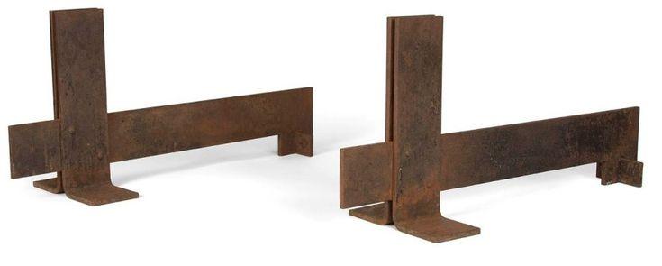 Dans le goût de Robert MALLET-STEVENS (1886-1945) Rare paire d'importants chenets modernistes en fer patiné. La façade est constituée de deux lames, montées en colonne, s'achevant au sol en équerre, formant ainsi piétement. Les jambages, formés d'une lame fixée par rivetage, débordent sur l'avant et se terminent, à l'arrière, en angle droit pour se conclure par une réception cruciforme. Oxydations. 35 x 23,5 x 75 cm