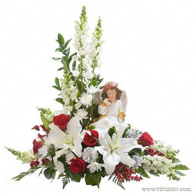 Heavenly Peace #40914B | Christmas keepsake angel floral arrangement with red roses and white lilies for sympathy and memorial. When considering funeral flower options, front-facing designs offer the best presentation, especially with keepsakes. For example, this L-shape allows the flowers to be seen rather than out of sight in the back.