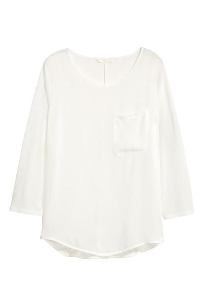 Bluză cu țesătură în față: Bluză din jerseu, cu crep șifon în față, cu mâneci trei sferturi, cu buzunar la piept și cu cusătură pe mijloc, la spate. Croială ușor rotunjită la bază, cu fente scurte pe laterale.