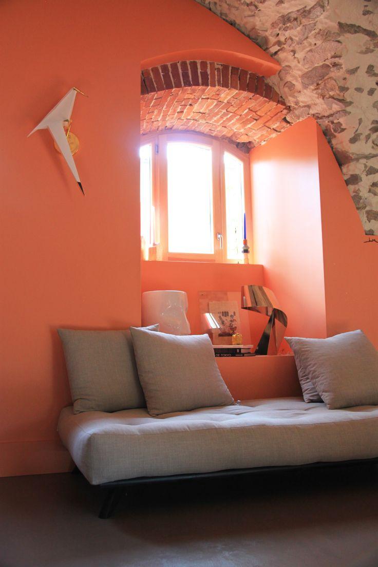 Décoration d'un salon dans une niche type bow window sous brique avec un plafond en voûte pierre ! Un joli luminaire en oiseau vient entre les deux fenêtres bois alu !