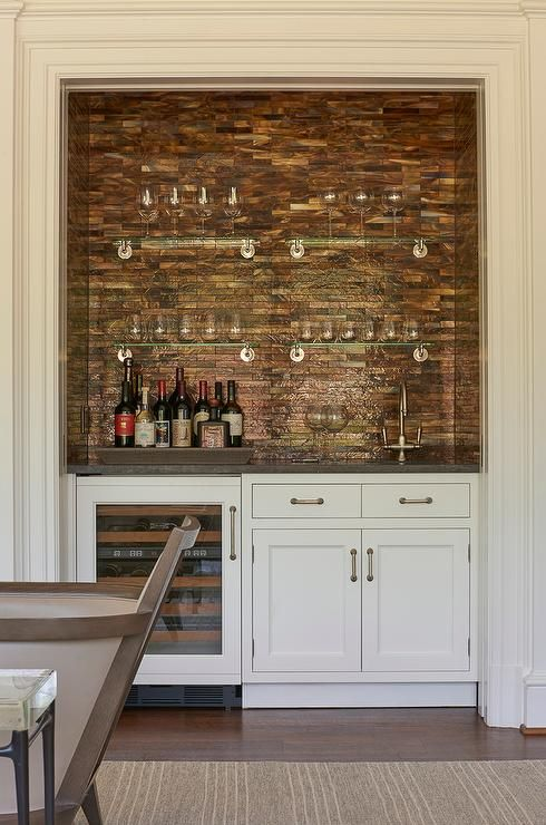 Living room bar nook is filled with white cabinets fitted with a wine cooler topped with gray quartz framing a sink under a shimmery copper mosaic tiled backsplash lined with stacked glass shelves.