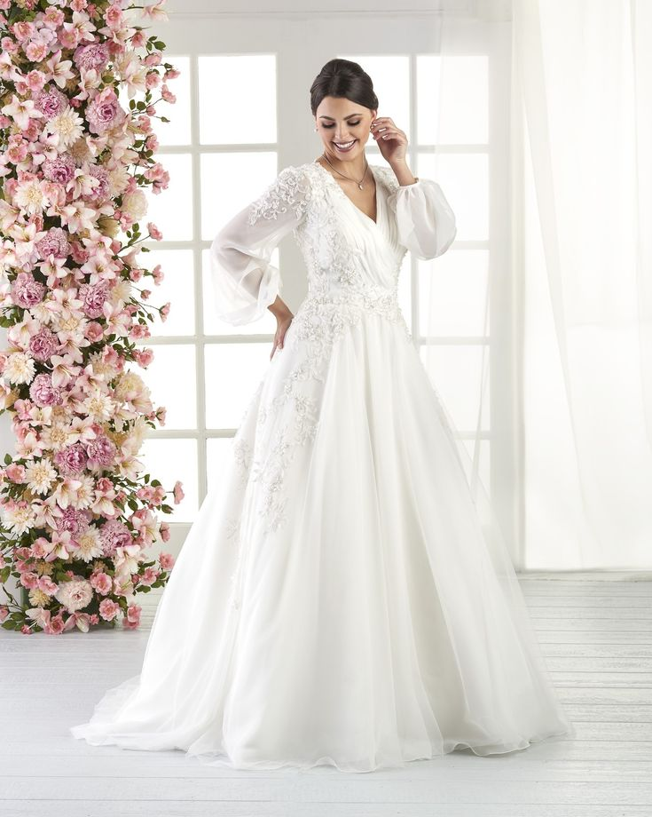 Product Name: 818 - Wedding Dresses | Bonny Bridal - The bishop sleeves of this style brings a traditional element to a modern gown. The shirred criss cross bodice is decorated with flowing floral appliqués. The detailed shoulders wrap to reveal the illusion button down back. The chiffon is softened with a top layer of tulle.