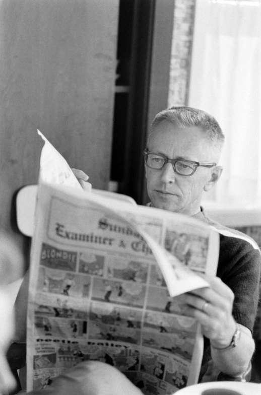 Charles M. Schulz, creator of Peanuts, reading the comics