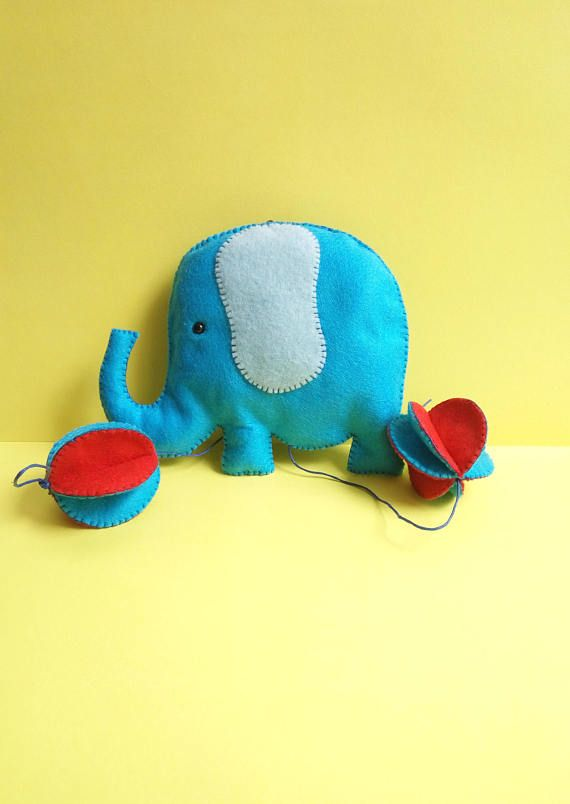 Color up your nursery or kids room with this cute elephant mobile wall hanging. You can also use it to decorate your baby shower or a kids birthday.  --Item details-- This mobile wall hanging is made out of high quality synthetic felt fabric. Everything is handmade by me, including the pattern design. It is hand cut and hand sewn. The elephant is one sided and features one safety eye. It is gently cotton filled and hangs from a cotton cord. You can choose colors between blue-red and…