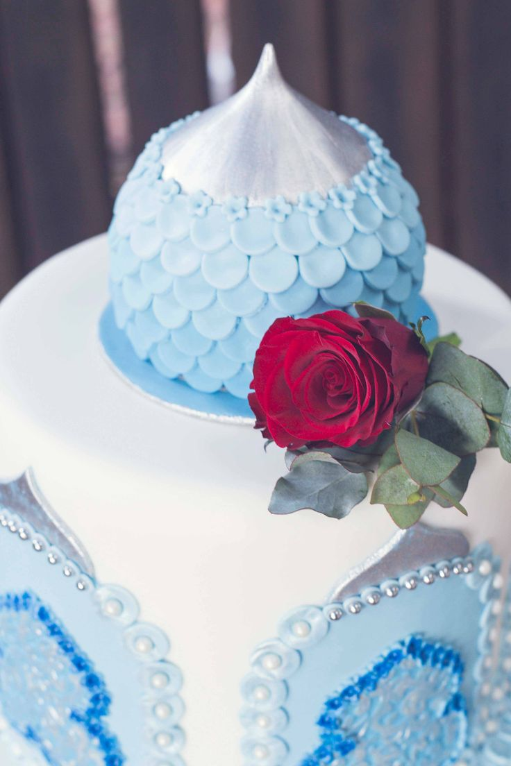 A simple red rose highlights the crisp whiteness of the wedding cake Photo: Kusjka du Plessis Cake: A Cake Story