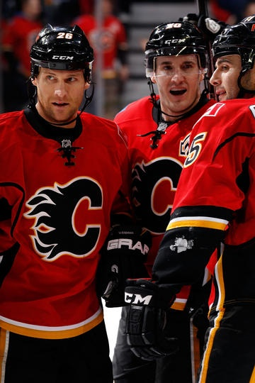 Dennis Wideman #26, Curtis Glencross #20 and Mark Giordano #5 of the Calgary Flames celebrate an overtime goal against the Phoenix Coyotes on April 12, 2013 at the Scotiabank Saddledome in Calgary, Alberta, Canada