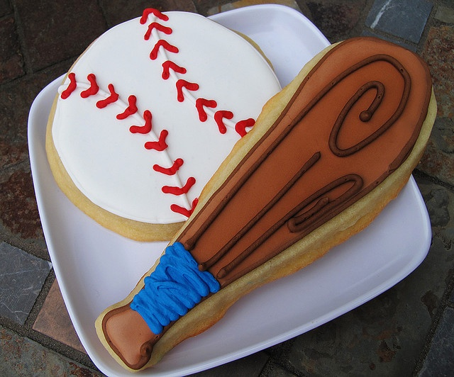 baseball cookies - wish there were directions but at least this can be used a model: medium and dark brown icing, blue, white and red icing and circle & bat shaped cutters on plain cookie dough.