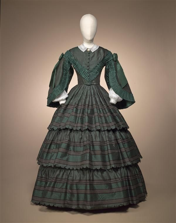Ca. 1860 blue/green shot silk dress trimmed with green ruching, flounces with green, black, and white stripes. Gemeente Museum, Netherlands.
