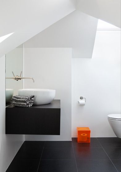 I love the dark floors with the white walls. I also love the sink and toilet. Everything is so clean, simple, and modern.