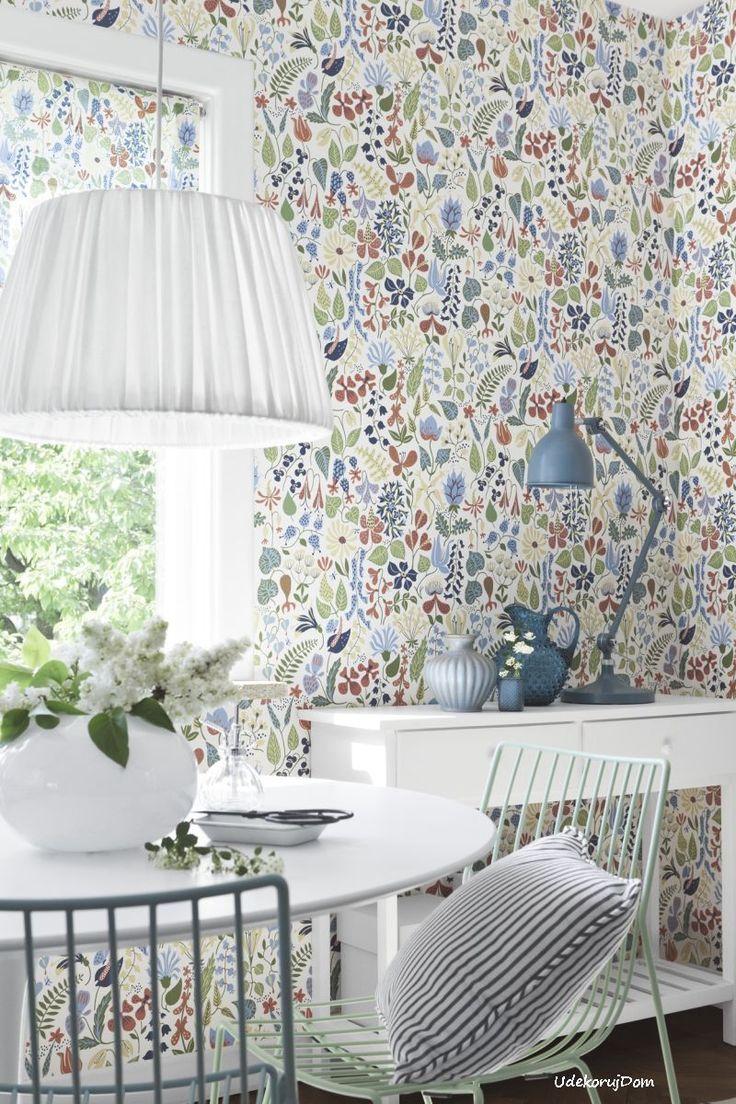 Kolorowa i radosna kuchnia skandynawska z tapetą w kwiatki. Uzupełniają ją białe i kolorowe dodatki.