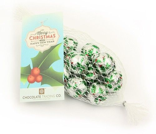 Net of chocolate holly balls by Chocolate Trading Co.  A net of milk chocolate holly balls (approximately 12 per net). Foil wrapped in a holly design and finished with a Merry Christmas & a Happy New Year gift tag. Perfect for Christmas stocking fillers, table settings and token corporate gifts. • Available to buy online as they are or choose to personalise the printed gift tag with your logo and message. Minimum order quantity for personalised labels x100 nets. Please call or email.