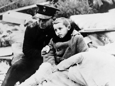 A uniformed Polish official comforts a boy whose mother was killed in an air raid on Warsaw, Sept., 1939. The boy himself was in wreckage for 12 hours before rescue crews liberated him. Poor thing :(