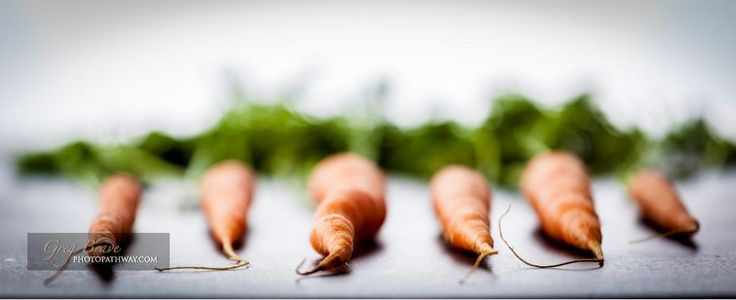 Six Dutch sweet carrots on bright textured stone background. Extremely shallow depth of field.