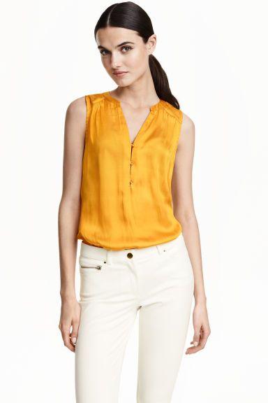 Blusa em cetim e jersey: Blusa sem mangas em cetim com costas em jersey macio e fluido. Tem decote em V com botões na parte superior e costas ligeiramente mais compridas.