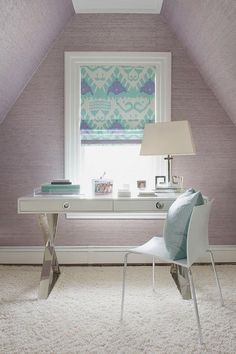 Chic purple and turquoise office features walls clad in purple grasscloth lined with a Jonathan Adler Channing Desk topped with a nickel Greek key lamp, Visual Comfort Kate Table Lamp, paired with a white sleek chair placed under a single window dressed in a purple and turquoise ikat roman shade in Quadrille Fabrics Kazak Aqua Lilac on White Fabric.