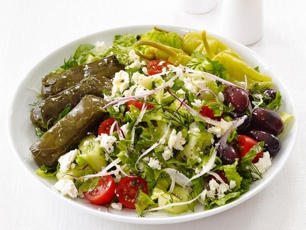 Toss romaine lettuce with olives, tomatoes, cucumbers and feta, then top with stuffed grape leaves to make this Greek Dinner Salad.