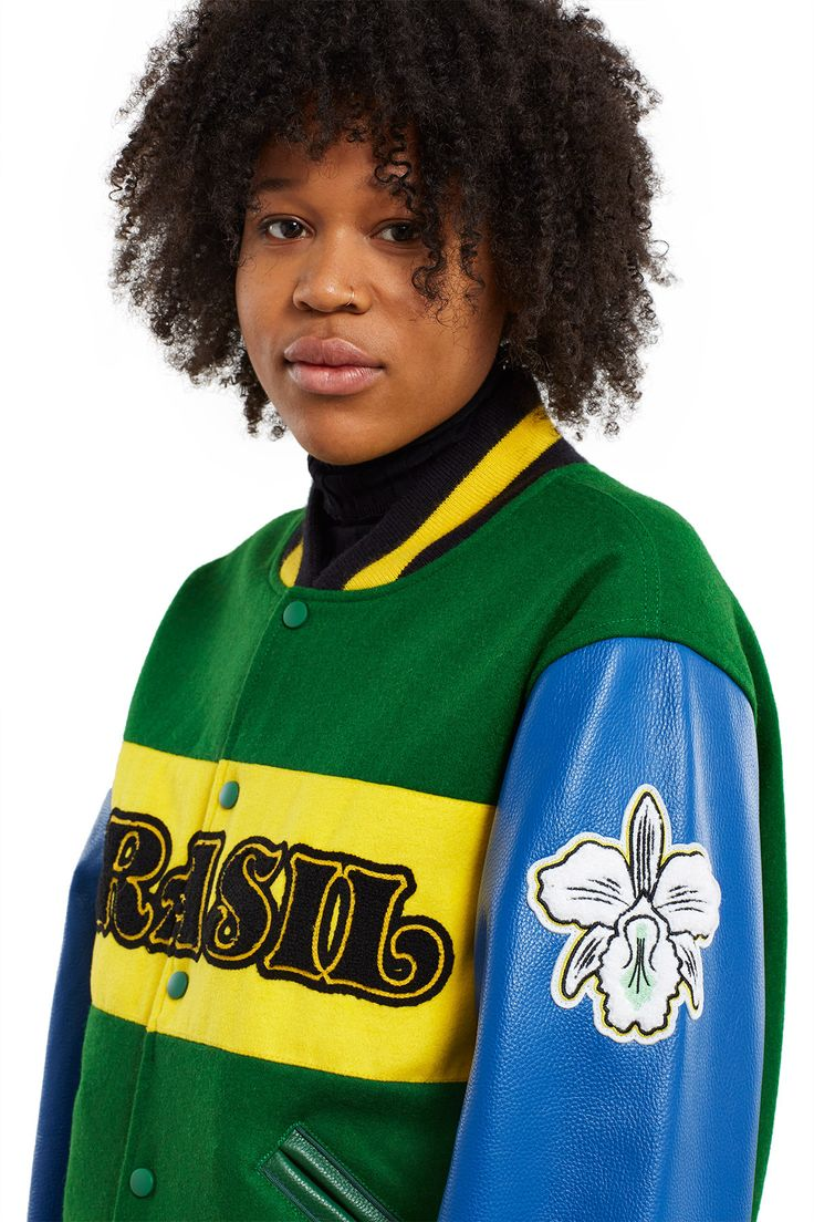 Opening Ceremony, Brazil Varsity Jacket The Brazil jacket is outfitted in the nation's flag colors—green for the forests, yellow for the country's mineral wealth, and blue for the sky over Rio de Janeiro on the day the nation was declared the Republic of Brazil. The jacket also sports the national flower corsage orchid, its national star emblem, and the mighty head of a jaguar at the back., Unisex, Front snap button closures, Leather sleeves, Ribbed collar, cuffs, and hem, Leather tri...