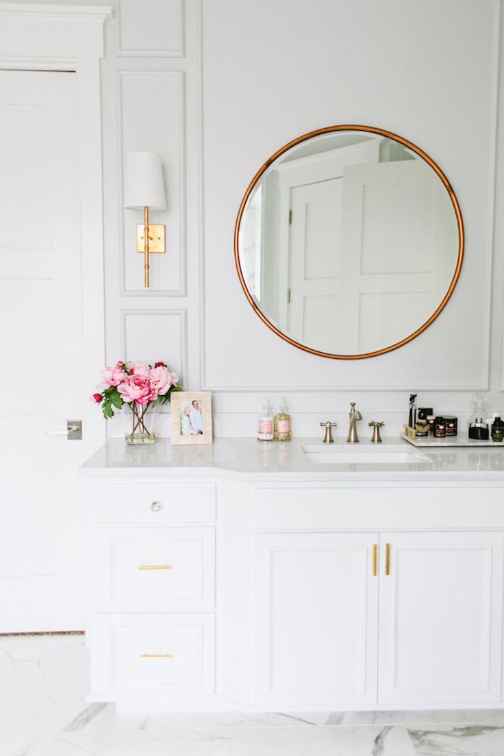 White bathroom vanity with brass pulls