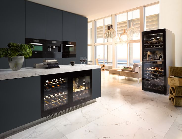 Another space for easy entertaining, this sleek kitchen features Miele Generation 6000 PureLine appliances in Obsidian Black and leads to a cosy seating area, ideal for after dinner drinks #kitchendesign