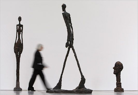 "A woman walked past the sculptures, from left, of ""Tall Woman III"", ""Walking Man II"" and ""Monumental Head"" by Alberto Giacometti at the Fondation Beyeler, Switzerland, in May 2009."