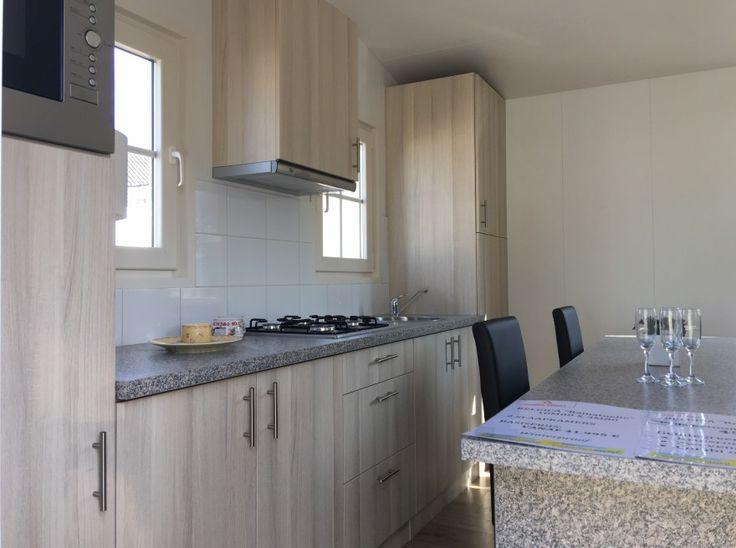 Moderne keuken in chalet voorzien van combi-magnetron, gaskooktoestel, koelkast en afzuigkap