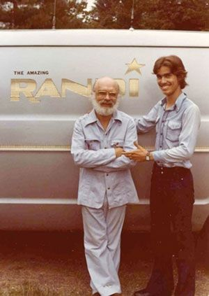 Randi with another man in front of a van with 'The Amazing Randi' painted on it