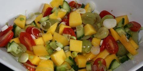 Eksotisk og sødmefuld salat med mango, vindruer, agurk og tomat samt forårsløg, der giver lidt kant.