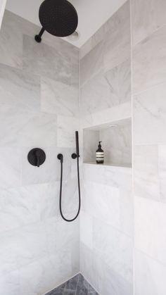 White Marble shower with black Dornbracht tapware and herringbone marble flooring. More
