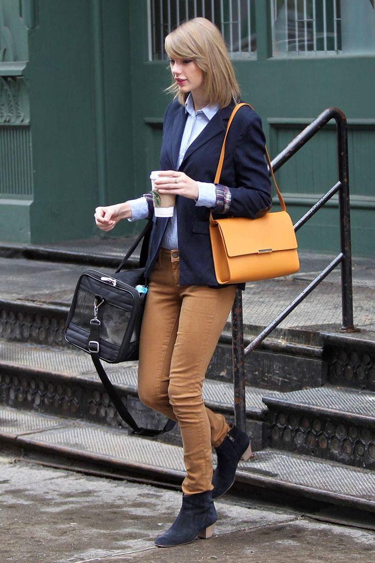 Taylor Swift - pantalón marrón, blazer azul marino sobre una camisa azul y botines de ante negros. Un bolso de color naranja-mostaza completó su look.