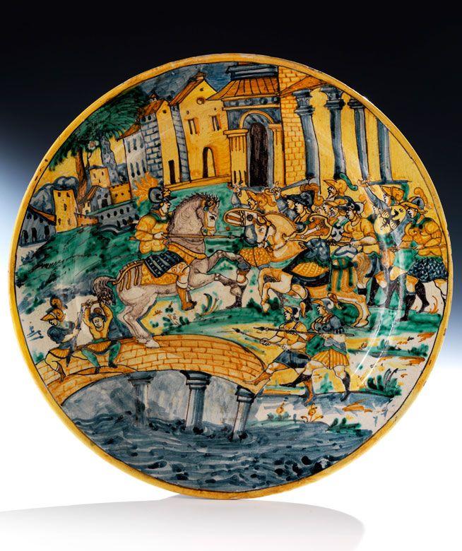Die Platte sanft gemuldet und mit kleiner Fahne. Das Istoriato-Dekor zeigt wohl die Schlacht an der Milvischen Brücke mit einem über die Brücke springenden ...