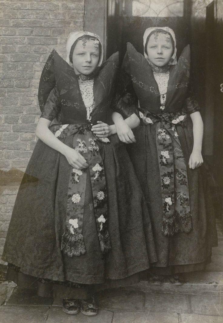 Twee meisjes in Axelse streekdracht. De meisjes zijn gekleed in zondagse dracht. Over de zwarte ondermuts en het oorijzer dragen ze een 'ronde muts' of 'hernhutter' (type muts), welke gedragen wordt tussen het 7e en 14e levensjaar. Aan de 'krullen' (oorijzeruiteinden) hangen 'dubbele strikken' (type oorijzerhangers). ca. 1942 #Zeeland #Axel