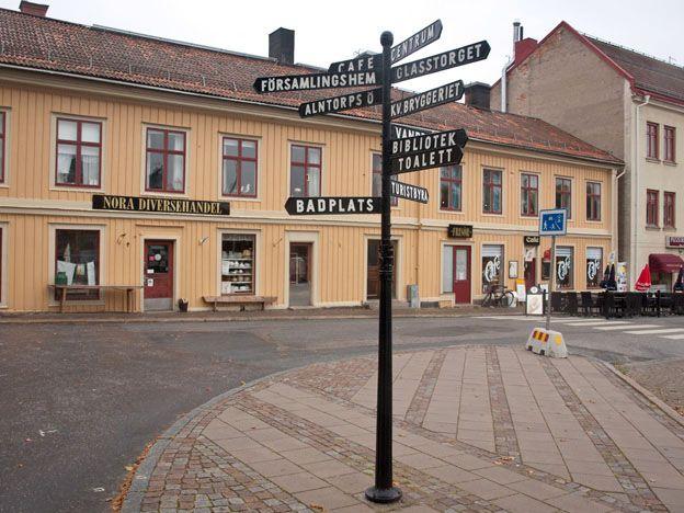 Nora, Sweden. Signposts on the square pointing to bathing place, library etc. - Ett torg med skyltar till badplats, bibliotek m.m