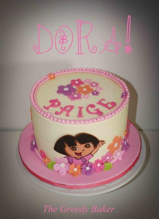 """A DORA the EXPLORER cake created for an aDORAble little girl! 8"""" rich chocolate cake with Neapolitan filling (one layer each of choc, vanilla & strawberry). Finished in buttercream with fondant accents. DORA image is hand cut from fondant with..."""