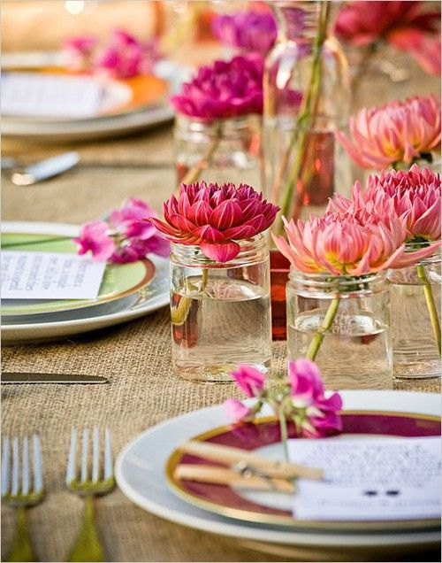 Basic glass jars serve as vases for individual settings. Mixed plates add another pop of color.