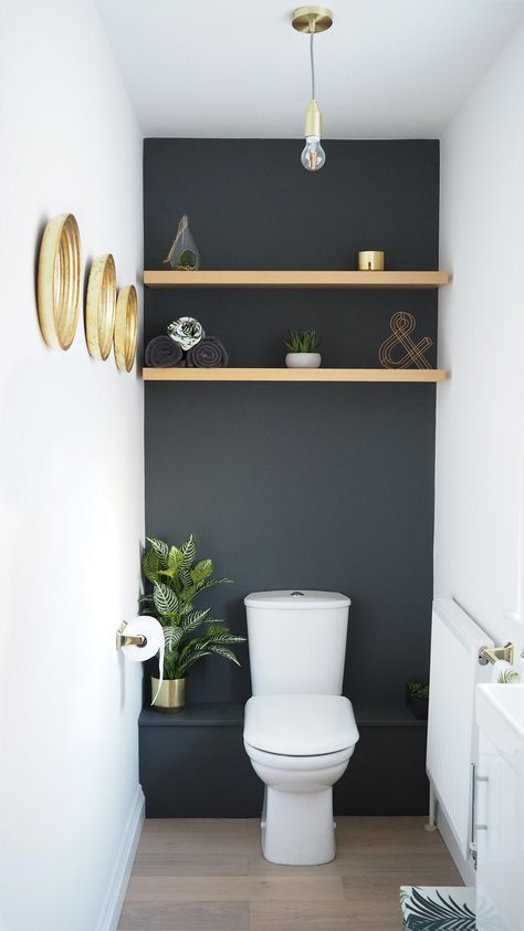 Dark grey downstairs bathroom diy home makeover with shelves in the alcoves and gold accents plus faux succulents and plants.