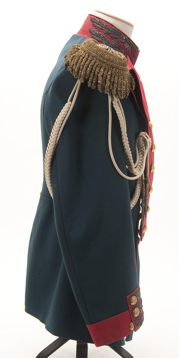 Right side view of and Imperial Russian tunic of a senior officer of the Moscovski Guard Infantry Regiment, circa 1907. Imperial green wool double breasted tunic with red collar, cuffs and piping. Collar and cuffs richly embroidered in a gold bullion oak leaf pattern, now age darkened, unique to this regiment. Has a matched pair of gold bullion epaulettes, faced in red, with applied silvered Nicholas II crowned ciphers, and a white adjutant's aiguillette with silver crowns and points.