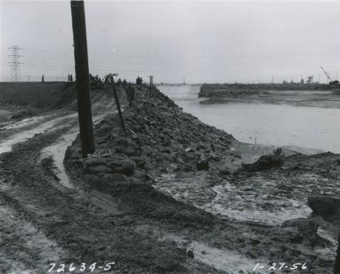 """A photo of construction on the Los Angeles River, January 27, 1956. Accompanying documentation places the location as """"Lower Los Angeles River-Carson to Willow"""" and provides the following description: """"Camera beneath P.E. Bridge at Sta. 253+25 and 480 feet left of centerline looking downstream (southwestward) along temporary dike at the entrance to paved section."""" Homer Halverson Collection. Water Works - Documenting Water History in Los Angeles."""