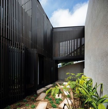An elevated entry bridge leads from the garage into a transitional space between the protective skin and the masonry structure.