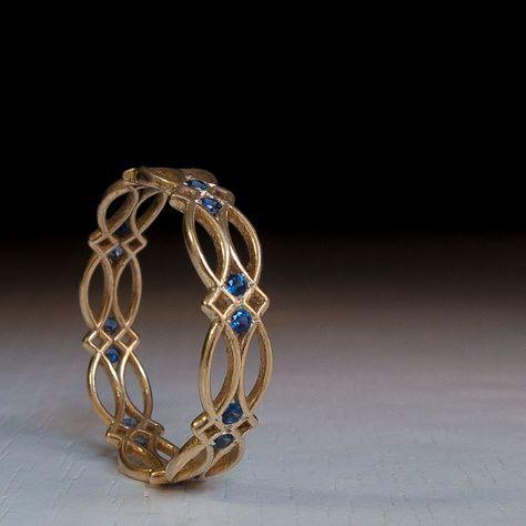 Un único anillo de la eternidad con un toque de algo celta. Hecho en oro macizo, su opción de quilates Conjunto con piedras naturales de 1,5 mm hermosos zafiros azul oscuro. Este anillo fue hecho a mano de principio a fin por un artista inspirado con un sincero objetivo de crear un anillo de oro diferentes de eternidad. Un vídeo de este anillo copia y pega esta url en tu navegador: https://youtu.be/GuO6_ZP9Q_I Está decorado con un patrón repetitivo de arcos y las piedras preci...